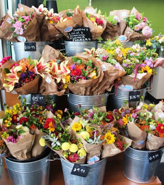 "A huge variety of Northwest-grown mixed bouquets labeled with ""American Flowers Week"" at New Seasons Market."